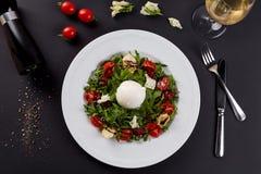 Σαλάτα φρέσκων λαχανικών στο άσπρο πιάτο στο Μαύρο Υγιής σαλάτα με τις ξηραμένες από τον ήλιο ντομάτες, Arugula, μοτσαρέλα και βα Στοκ εικόνα με δικαίωμα ελεύθερης χρήσης
