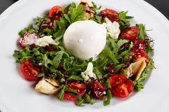 Σαλάτα φρέσκων λαχανικών στο άσπρο πιάτο στο Μαύρο Υγιής σαλάτα με τις ξηραμένες από τον ήλιο ντομάτες, Arugula, μοτσαρέλα και βα Στοκ Εικόνες