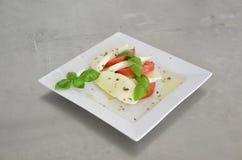Σαλάτα Caprese με τις ντομάτες, το βασιλικό και τη μοτσαρέλα στον πίνακα του ανοξείδωτου Στοκ Φωτογραφίες