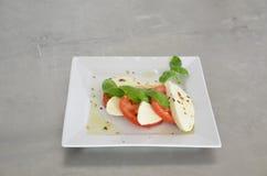 Σαλάτα Caprese με τις ντομάτες, το βασιλικό και τη μοτσαρέλα στον πίνακα του ανοξείδωτου Στοκ Φωτογραφία