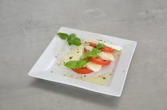 Σαλάτα Caprese με τις ντομάτες, το βασιλικό και τη μοτσαρέλα στον πίνακα του ανοξείδωτου Στοκ Εικόνες