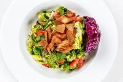 Σαλάτα Fattoush ή ψωμιού με croutons pita, φρέσκα λαχανικά και χορτάρια, στο άσπρο πιάτο στον ξύλινο πίνακα με το sumac, λεμόνι στοκ φωτογραφία
