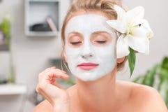 Σαλόνι SPA Όμορφη γυναίκα με την του προσώπου μάσκα αργίλου στο σαλόνι ομορφιάς Στοκ φωτογραφία με δικαίωμα ελεύθερης χρήσης