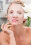 Σαλόνι SPA Όμορφη γυναίκα με την του προσώπου μάσκα στο σαλόνι ομορφιάς Στοκ Εικόνες