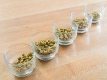 Σβόλοι λυκίσκων στο φλυτζάνι γυαλιού για την παρασκευή της μπύρας στοκ εικόνες