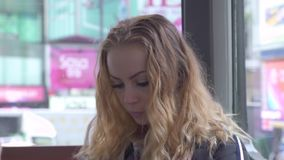 Σγουρή γυναίκα προσώπου που φαίνεται κινητό τηλέφωνο οδηγώντας το εσωτερικό αστικό τραμ στη σύγχρονη πόλη Νέα χρησιμοποίηση γυναι απόθεμα βίντεο