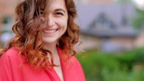 Σγουρή στροφή τρίχας πιπεροριζών γυναικών χαμόγελου Flirty χαριτωμένη απόθεμα βίντεο