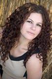 Σγουρή τρίχα, θηλυκό πρότυπο brunette στην ψηλή χλόη Στοκ Φωτογραφία