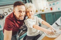 Σγουρή χαριτωμένη να ζυμώσει αγοριών ζύμη για την πίτα με τη γονική καθοδήγηση στοκ φωτογραφίες με δικαίωμα ελεύθερης χρήσης