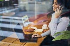 Σγουρός αφροαμερικάνος σε ένα γκρίζο σακάκι που χρησιμοποιεί την ασύρματη σύνδεση στον καφέ Στοκ Εικόνες
