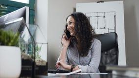 Σγουρός θηλυκός αρχιτέκτονας τρίχας που μιλά στο έξυπνο τηλέφωνο και που χαμογελά κατά τη διάρκεια της ημέρας εργασίας στο γραφεί απόθεμα βίντεο