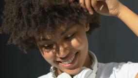 Σγουρός-μαλλιαρή κυρία στα ακουστικά που φλερτάρουν και που χαμογελούν ειλικρινά, σχετικά με την τρίχα απόθεμα βίντεο