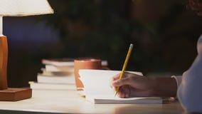 Σγουρός-μαλλιαρή συνεδρίαση κοριτσιών στον καφέ, που γράφει ένα ημερολόγιο για τα όνειρα και τις μνήμες της φιλμ μικρού μήκους