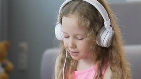 Σγουρός-μαλλιαρό κορίτσι της Νίκαιας που ακούει τη μουσική στα ακουστικά και τα τραγούδια τραγουδιού απόθεμα βίντεο