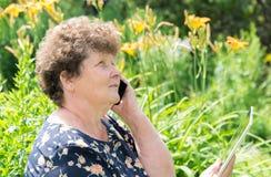 Σγουρός-μαλλιαρή γυναίκα με το τηλέφωνο και την ταμπλέτα κυττάρων έξω Στοκ Φωτογραφία