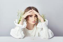 Σγουρός ξανθός ρομαντικός κοιτάζει, όμορφα μάτια Άσπρα wildflowers στα χέρια Άσπρο ελαφρύ φόρεμα κοριτσιών και σγουρή τρίχα, πορτ στοκ εικόνες