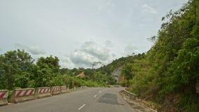 Σγουρός δρόμος ασφάλτου βουνών από τις εγκαταστάσεις με τα εμπόδια φιλμ μικρού μήκους