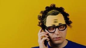 Σγουρός τύπος που μιλά σοβαρά στο smartphone, στο κίτρινο υπόβαθρο τοίχων, τις μαύρες τρίχες φιλμ μικρού μήκους