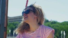Σγουρό κορίτσι σε μια ταλάντευση σε ένα θερινό πάρκο απόθεμα βίντεο