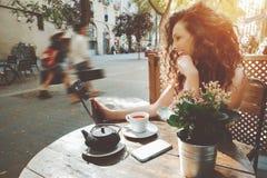 Σγουρό κορίτσι στον καφέ οδών Στοκ Φωτογραφία