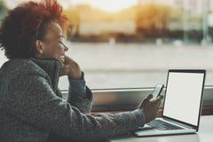Σγουρό μικτό κορίτσι με το lap-top και το smartphone Στοκ εικόνες με δικαίωμα ελεύθερης χρήσης