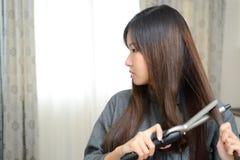 σγουρό τρίχωμα Όμορφη ασιατική γυναίκα με μακρυμάλλη σιδερώνοντας το, Usi Στοκ εικόνες με δικαίωμα ελεύθερης χρήσης