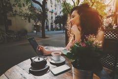 Σγουρό χαμογελώντας όμορφο κορίτσι που χρησιμοποιεί την ψηφιακή ταμπλέτα στον καφέ Στοκ φωτογραφία με δικαίωμα ελεύθερης χρήσης