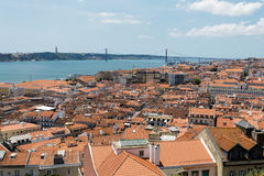 Σειρά ή κόκκινες στέγες κεραμιδιών των σπιτιών στη Λισσαβώνα και τον ποταμό Στοκ Εικόνες