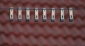 Σειρά συνδετήρων υφασμάτων στην κορυφή στεγών με τη στέγη στο υπόβαθρο στοκ εικόνες