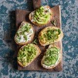 Σειρά των υγιών σάντουιτς με το αβοκάντο, το hummus, το ricotta, το αγγούρι, τους νεαρούς βλαστούς ηλίανθων, τα πράσινα μικροϋπολ Στοκ Φωτογραφία