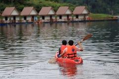 Σειρά δύο αδελφών ένα καγιάκ στη λίμνη στο φράγμα Ratchaprapa Στοκ Φωτογραφία