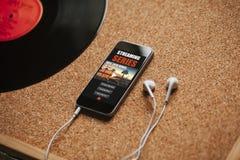 Σειρά app ροής σε μια κινητή τηλεφωνική οθόνη, κοντά στα άσπρα ακουστικά σε έναν καφετή πίνακα Στοκ φωτογραφίες με δικαίωμα ελεύθερης χρήσης