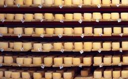 Σειρές στα ράφια με τη γήρανση του τυριού στο κελάρι Στοκ Φωτογραφίες