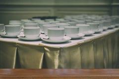 σειρές του άσπρων φλυτζανιού και του κουταλιού για το τσάι υπηρεσιών ή καφές στο breakfa Στοκ Εικόνες