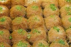 Σειρές του γλυκού τουρκικού επιδορπίου kunefe με τη σκόνη φυστικιών, ζύμη Kataifi, στην οδό αγοράς Στοκ Εικόνες
