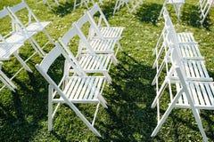 Σειρές του λευκού που διπλώνουν τις καρέκλες στο χορτοτάπητα Στοκ Φωτογραφίες