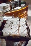 Σειρές του καθαρών άσπρων φλυτζανιού και του πιατακιού με το κουταλάκι του γλυκού Στοκ Εικόνες