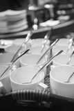 Σειρές του καθαρών άσπρων φλυτζανιού και του πιατακιού με το κουταλάκι του γλυκού Στοκ Φωτογραφίες