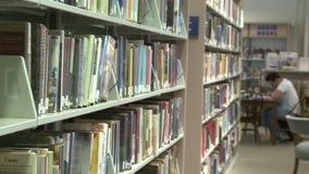 Σειρές των βιβλίων στα ράφια στη βιβλιοθήκη (1 3) απόθεμα βίντεο
