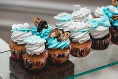Σειρές των γενεθλίων cupcake με τη βουτύρου άσπρη και μπλε τήξη κρέμας σε μια στάση γυαλιού Στοκ Φωτογραφίες