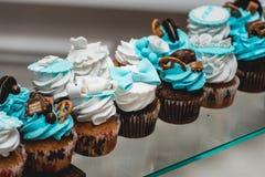 Σειρές των γενεθλίων cupcake με τη βουτύρου άσπρη και μπλε τήξη κρέμας σε μια στάση γυαλιού Στοκ φωτογραφίες με δικαίωμα ελεύθερης χρήσης