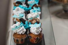 Σειρές των γενεθλίων cupcake με τη βουτύρου άσπρη και μπλε τήξη κρέμας σε μια στάση γυαλιού Στοκ φωτογραφία με δικαίωμα ελεύθερης χρήσης