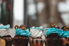 Σειρές των γενεθλίων cupcake με τη βουτύρου άσπρη και μπλε τήξη κρέμας σε μια στάση γυαλιού Στοκ Εικόνες