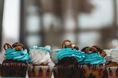 Σειρές των γενεθλίων cupcake με τη βουτύρου άσπρη και μπλε τήξη κρέμας σε μια στάση γυαλιού Στοκ Φωτογραφία