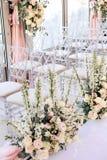 Σειρές των διαφανών καρεκλών που διακοσμούνται με τις συνθέσεις λουλουδιών των τριαντάφυλλων και των άσπρων νεραγκουλών στην περι στοκ εικόνες