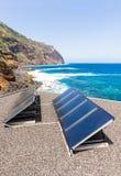 Σειρές των ηλιακών συσσωρευτών στη στέγη στην παραλία και τη θάλασσα Στοκ Φωτογραφία