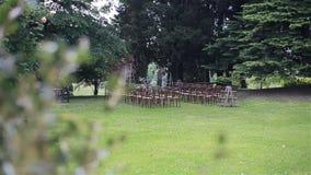 Σειρές των καρεκλών στο χορτοτάπητα έτοιμο για την υπαίθρια γαμήλια τελετή απόθεμα βίντεο