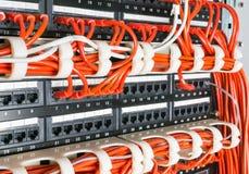 Σειρές των καλωδίων δικτύων που συνδέονται με την πλήμνη δρομολογητών και διακοπτών Στοκ Φωτογραφία