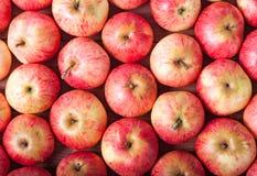 Σειρές των κόκκινων μήλων σε μια ξύλινη επιφάνεια Τοπ όψη Στοκ Εικόνες