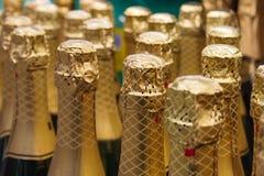 Σειρές των μπουκαλιών με τη σαμπάνια στο χρυσό φύλλο αλουμινίου στοκ φωτογραφίες